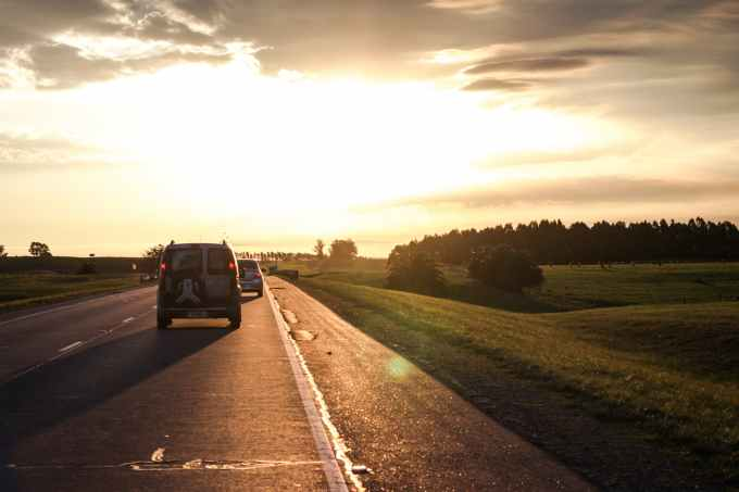 photo of vehicles on road during golden hour